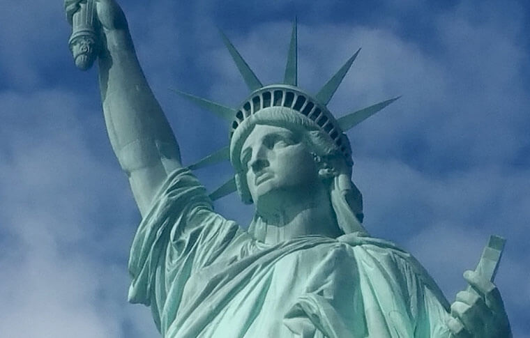 statues of liberty head and shoulders with blue sky behind